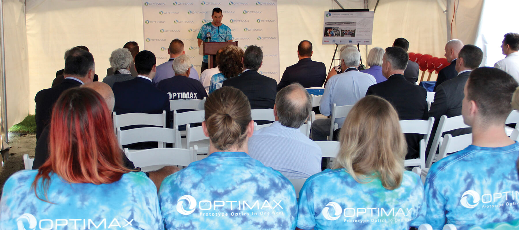 Optimax team in tie dye uniform during groundbreaking expansion